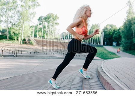 Photo Of Curly-haired Athletic Woman Running Through Park Among Benches On Summer Day. Tinting Under