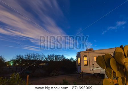 Clouds Floating In A Dark Blue Sky Over A Camper Trailer Parked In A Desert Landscape Location.