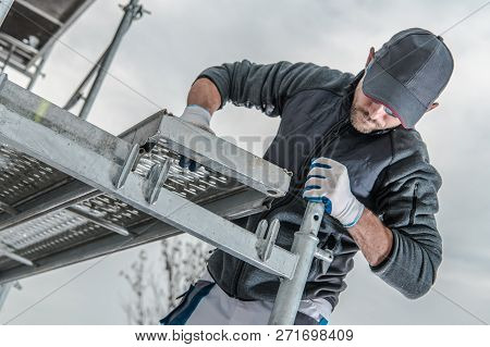 Caucasian Construction Worker Installing Scaffolding Elements. Industrial Theme