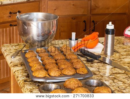 Healthy Muffins Cooling Down On A Marble Or Granite Kitchen Countertop. Kitchen Utensils And Wooden