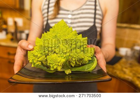 Bright Green And Yellow Romanesco Broccoli On A Plate Held By Woman In Apron In Kitchen.