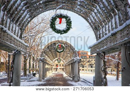 Wooden Arch With A Christmas Wreath.park Alley With Christmas Decorations On A Snowy Day