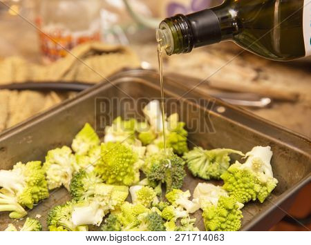 Olive Oil Being Poured Onto Fresh Romanesco Broccoli In A Metal Pan. Kitchen Setting.