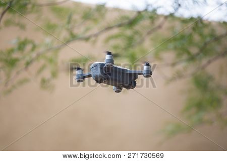Drone With Four Propellers Flying Through The Air Near Tree Branches And A Building.