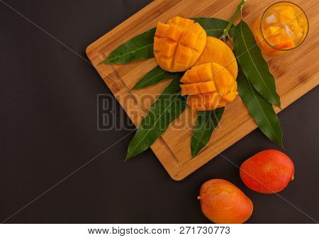 Mango Fruit And Mango Drink On The Wooden Cutting Board. Tropical Fruit Concept With A Huge Amount O