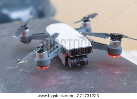 Photography Drone With Four Propellers Parked With Red Lights Lit Up Underneath Propellers.