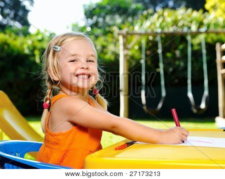 cute blonde girl with pigtails smiles with joy while drawing with crayons at kindergarten