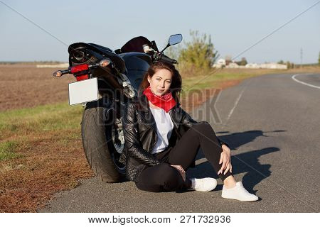 Relaxed Carefree Female Motorcyclist Wears Black Clothes And White Trainers, Sits At Asphalt Near Mo