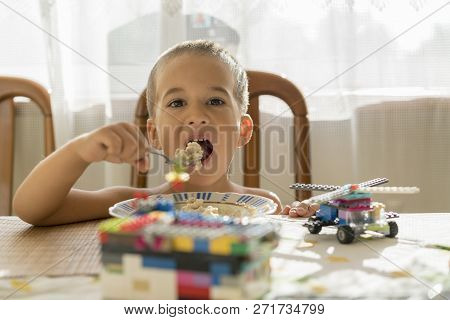 The Boy 4years Eats Porridge. Childrens Table. The Concept Of The Childs Independence. Happy Little