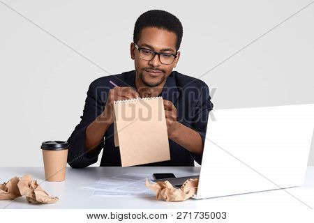 Shot Of Serious Black Man Journalist Works On Creation New Article, Writes Down Ideas In Spiral Note