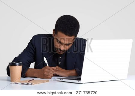 Busy Male Worker With Dark Healthy Skin, Writes Down Information In Papers, Holds Pen, Wears Black S