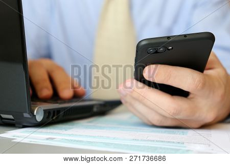 Businessman In Tie Works In Office, Sitting At A Table With Laptop And Smartphone In Hand. Male Hand