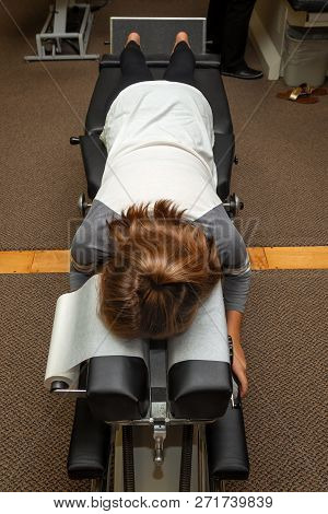 A young girl lays on her stomach on a Chiropractic adjustment table waiting for the Chiropractor to come work on her. poster