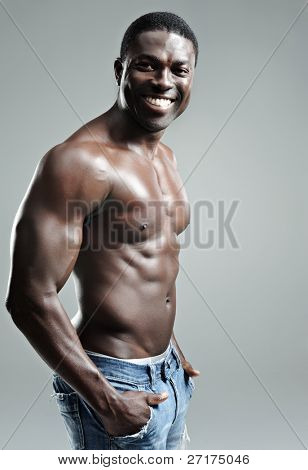 Fit black model topless in studio, on grey background