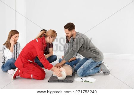 Group Of People With Instructor Practicing Cpr On Mannequin At First Aid Class Indoors