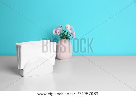 Ceramic Napkin Holder With Paper Serviettes And Flowers In Vase On Table. Space For Text
