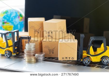 Mini Forklift Truck Load Cardboard Box, Stack Of Coins And Pile Of Boxes On Laptop Keyboard With Glo
