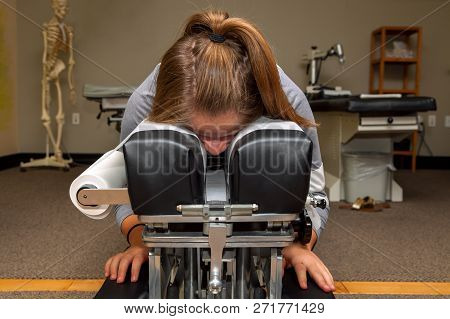 A Young Girl Waits On A Tilting Chiropractic Table With Her Face Down In A Crack In The Table.  Ther
