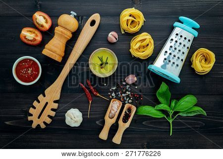 The  Pasta On Black Wooden Background. Yellow Italian Pasta With Ingredients. Italian Food And Menu
