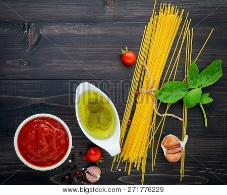 The Thin Spaghetti On Black Wooden Background. Yellow Italian Pasta With Ingredients. Italian Food A