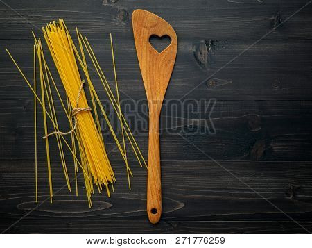The Thin Spaghetti On Black Wooden Background. Yellow Italian Pasta With Copy Space . Italian Food A