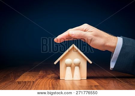 Family Life And Property Insurance Concept. Wooden Figurines Representing Family And Wooden House An