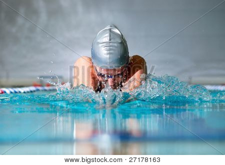 woman swims using the breaststroke in indoor pool