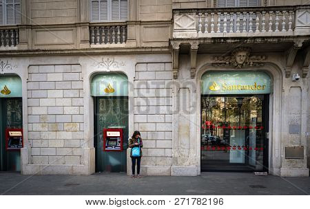 Barcelona, Spain - December 2018: Unnidentified Person Uses An Atm Machine At Santander Bank On Pass