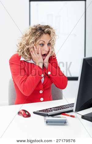 Oh no - shocked business woman in front of computer in the office