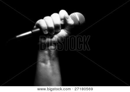 Gray Scale Microphone Clinched Firmly in Male Fist on a Black Background.