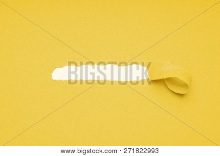 Hole Ripped In Yellow Paper Background To Reveal Hidden Copy Space Underneath