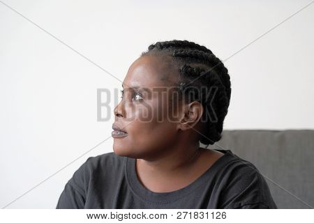 Lonely African Woman Is Sad Sitting On The Bed. Portrait Of A Beautiful Sad Girl Closeup. Woman Feel