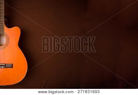 Six-string Acoustic Guitar On A Dark Brown Background. Classical Spanish Guitar. Musical Instrument.