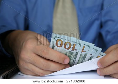Male Hands Holding An Envelope With Dollars, Close-up. Clerk Or Businessman Takes The Money In Offic
