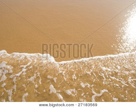 sun mirrored in the wet sand beach at summer
