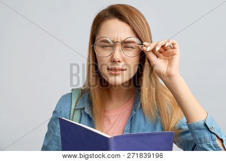 Beautiful Young Blonde Girl Holding Glasses And Squinting Trying To Read The Inscription In Front Of