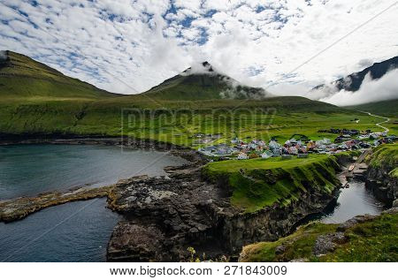 Picturesque Little Village In Front Of Mountains And Cloudy Sky