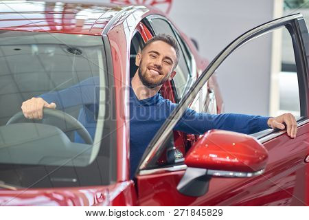 Young Handsome Man Almost Sitting In Red Car And Closing Front Door. Brunette Client In Car Salon Sm