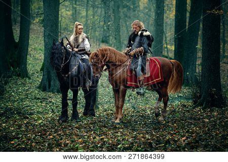 Warriors Woman An Man On Horses In The Woods. Scandinavian Vikings Riding Horse With Axes In Hands.