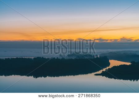 Early blue sky reflected in river water. Riverbank with forest under predawn sky. Yellow stripe in picturesque sky. Fog hid trees on island. Mystical morning atmospheric landscape of majestic nature. poster