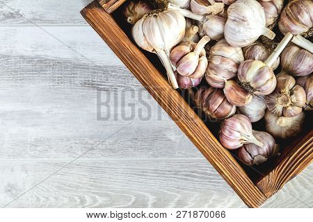 Garlic In A Wooden Box. Fresh Garlic On A Black Stone Surface, Top View, Copy Space, Free Space For