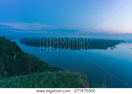 Mystical view from high shore on broad river with smooth water. Riverbank of large island with forest under mist. Early haze above trees. Morning atmospheric landscape of majestic nature in blue tone. poster