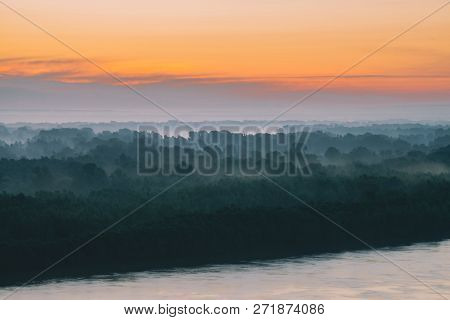 Mystical view on riverbank of large island with forest under haze at early morning. Mist among layers from tree silhouettes under warm predawn sky. Morning atmospheric landscape of majestic nature. poster