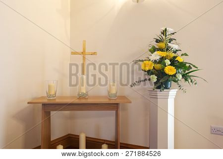 Interior Of A Crematorium Chapel With Flowers, Cross And Candles