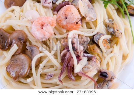 spaghetti with seafood and mushrooms on white plate poster