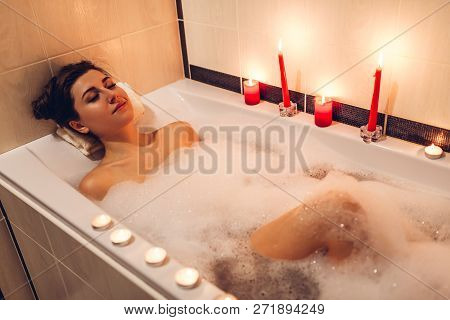 Young Woman Lying In Bath Tub And Relaxing With Foam And Candles Enjoying Spa Procedure At Home
