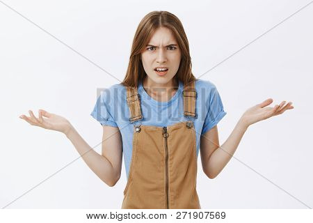 Waist-up Shot Of Perplexed And Confused Pissed Girlfriend In Brown Dungarees Shrugging Raising Palms