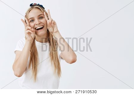 Portrait Of Cute And Funny Carefree Caucasian Female Student In White Shirt Smiling Joyfully And Sho