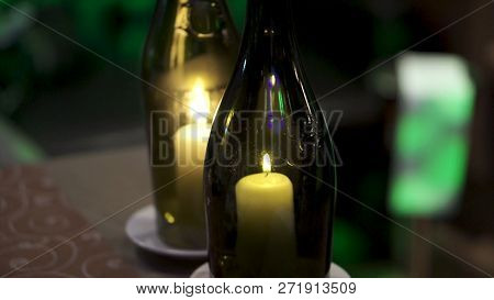 Decorative Bottles With Candles Inside. Clip. Beautiful Stylish Candles In The Bottles. A Candle Bur