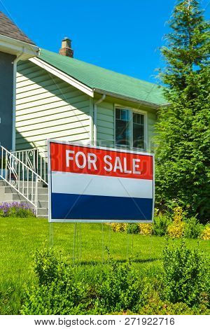 Real Estate Sign 'for Sale' On Front Yard Of A House